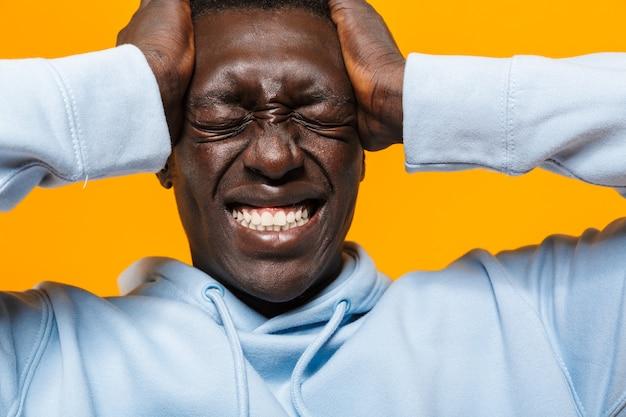 Bild eines angespannten afroamerikaners im streetwear-hoodie, der leidet und sich den kopf greift