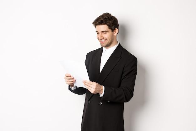 Bild eines attraktiven geschäftsmannes im schwarzen anzug, der ein dokument liest und lächelt, an einem bericht arbeitet und vor weißem hintergrund steht