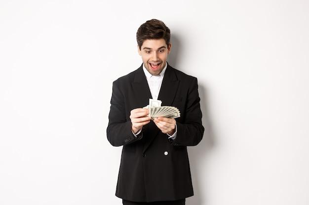 Bild eines aufgeregten gutaussehenden geschäftsmannes, der geld zählt und amüsiert lächelt, vor weißem hintergrund im anzug steht