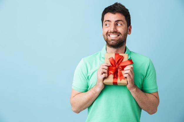 Bild eines aufgeregten jungen, gutaussehenden bärtigen mannes, der isoliert über der blauen wand posiert, die eine geschenkbox hält.