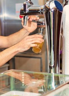 Bild eines barkeepers, der gezapftes bier in ein glas in einer kneipe oder in einem restaurant gießt