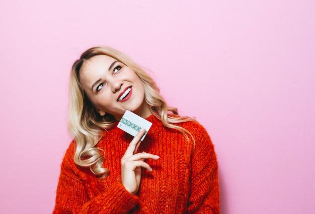 Bild eines blonden mädchens, das eine kreditkarte hält und im raum auf einer rosa wand lächelt