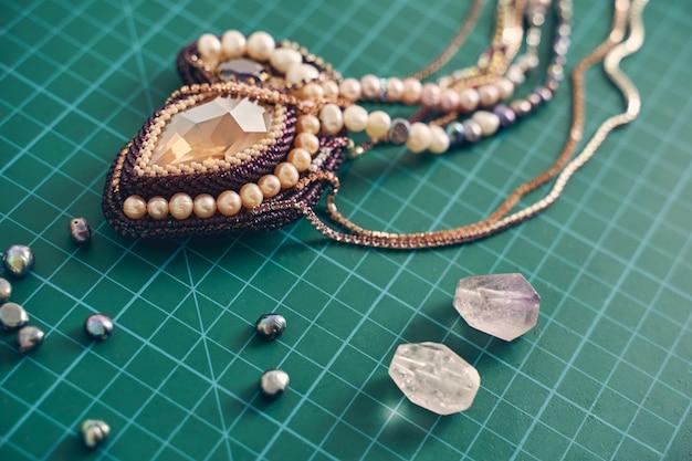 Bild eines dekorativen, eleganten luxus-design-anhängers mit mehrfarbigen perlen und braunem stein