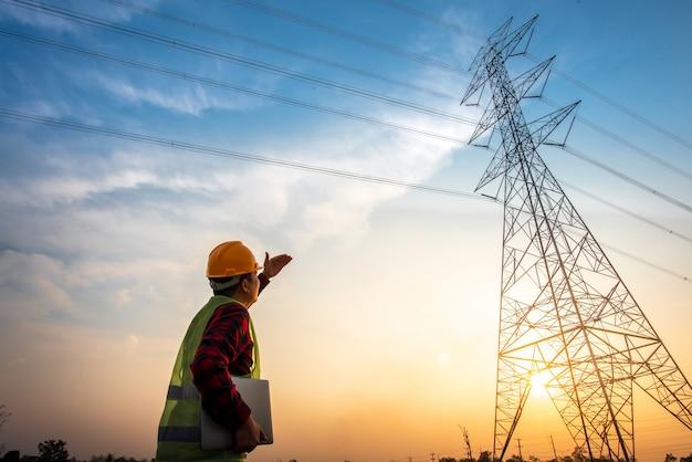 Bild eines elektrotechnikers, der am elektrizitätswerk steht und zuschaut, um die planungsarbeiten durch stromerzeugung an hochspannungsstrommasten zu betrachten.