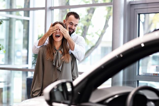 Bild eines erwachsenen mannes, der eine schöne frau im autohaus überrascht