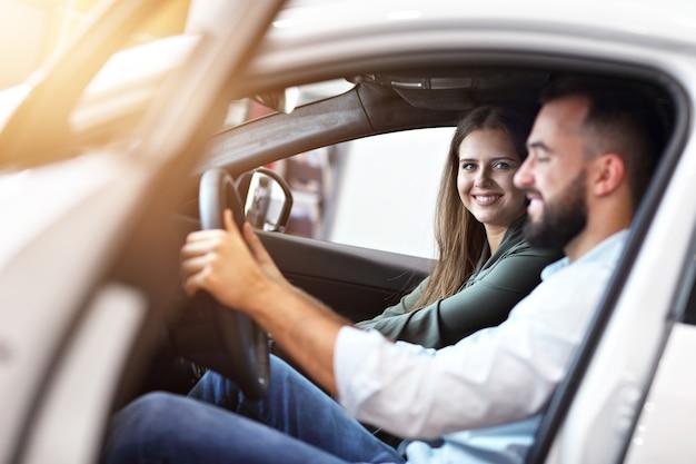 Bild eines erwachsenen paares, das sich im ausstellungsraum für ein neues auto entscheidet