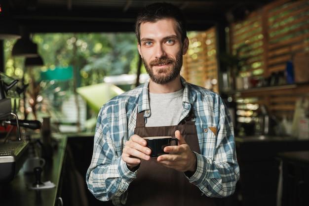 Bild eines freundlichen barista-mannes mit schürze, der kaffee macht, während er im café oder kaffeehaus im freien arbeitet?