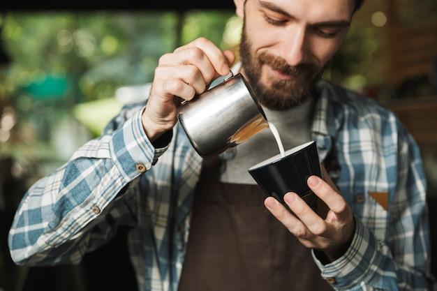 Bild eines fröhlichen barista-mannes mit schürze, der kaffee macht, während er im café oder kaffeehaus im freien arbeitet?