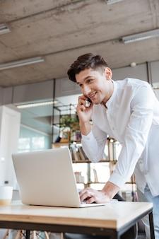 Bild eines fröhlichen jungen mannes in weißem hemd mit laptop-computer beim telefonieren. coworking. sieh zur seite.