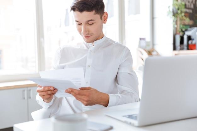 Bild eines fröhlichen mannes, der in weißem hemd gekleidet ist und dokumente hält, während er einen laptop verwendet. coworking. dokumente anschauen.