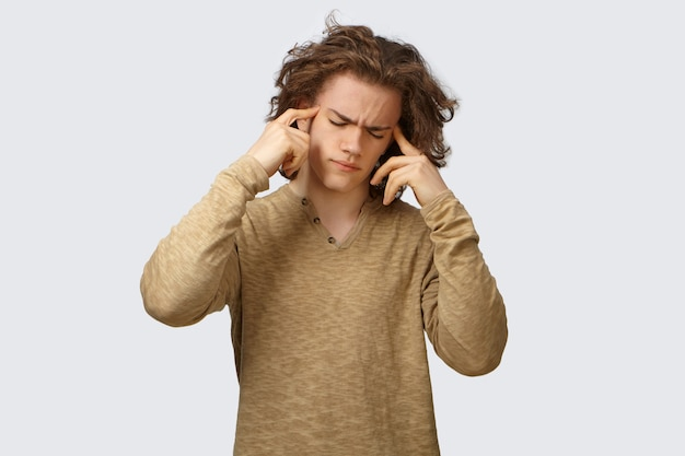 Bild eines frustrierten, gestressten, kranken, jungen, kaukasischen mannes, der sich wegen schrecklicher kopfschmerzen deprimiert fühlt, die stirn runzelt, die augen geschlossen hält und die finger auf seine schläfen drückt, um den schmerz zu lindern