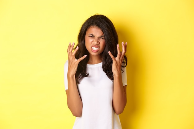 Bild eines frustrierten und wütenden afroamerikanischen mädchens, das eine grimasse verzieht und die hände zittert