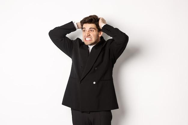 Bild eines frustrierten und wütenden geschäftsmannes im schwarzen anzug, der sich die haare am kopf reißt und das gesicht verzieht, nach links in die katastrophe schaut und vor weißem hintergrund angespannt steht