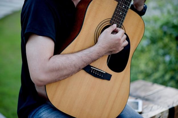 Bild eines gitarristen, ein junger mann, der eine gitarre beim sitzen in einem natürlichen garten spielt