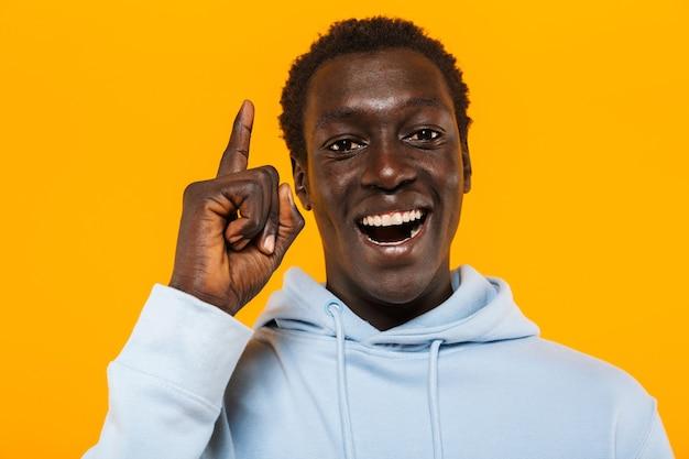 Bild eines glücklichen afroamerikaners im streetwear-hoodie, der lächelt und mit dem finger nach oben als ideenzeichen zeigt