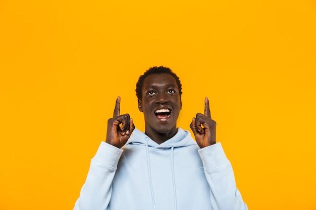 Bild eines glücklichen afroamerikaners im streetwear-hoodie, der lächelt und mit den fingern nach oben auf das exemplar zeigt