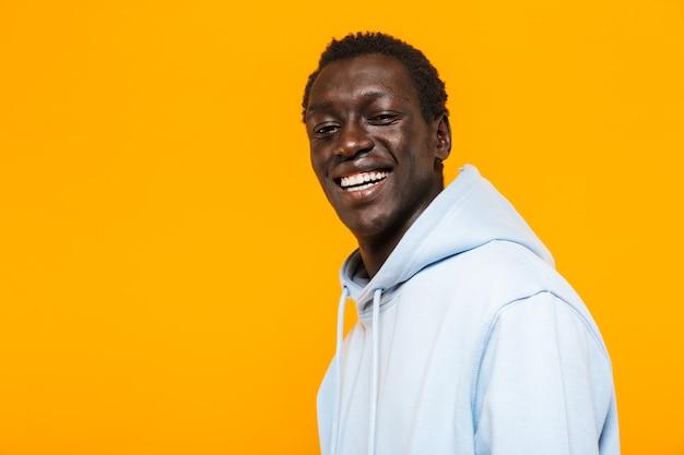 Bild eines glücklichen afroamerikaners im streetwear-hoodie, der steht und lächelt