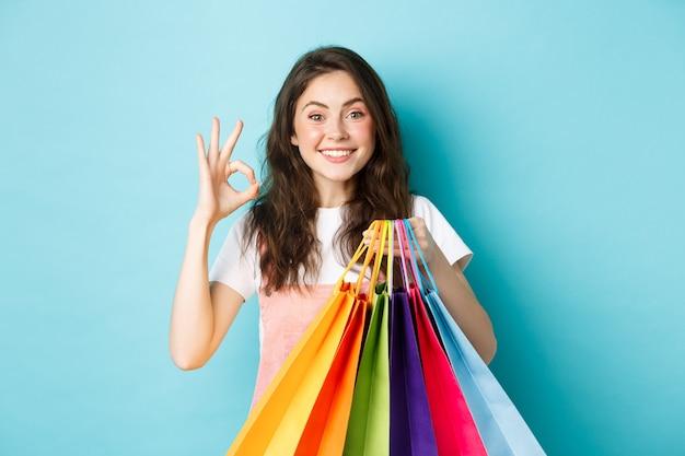 Bild eines glücklichen jungen glamour-frauenladens in geschäften mit rabatten, der ein okayzeichen zeigt, einkaufstüten hält, aufgeregt in die kamera schaut, blauer hintergrund