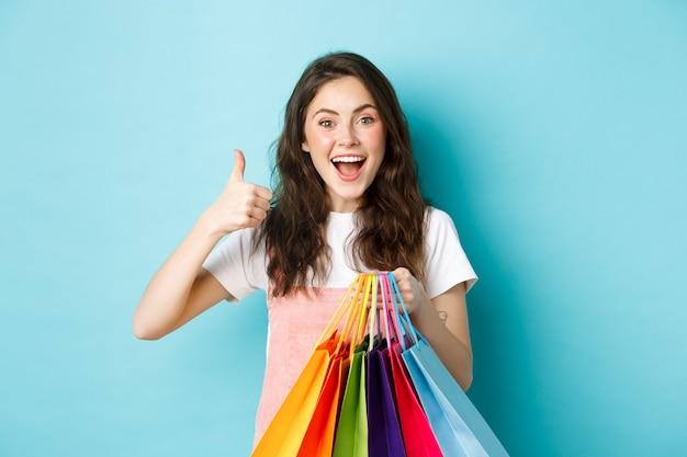 Bild eines glücklichen jungen glamour-frauenshops in geschäften mit rabatten, daumen nach oben zeigend, einkaufstaschen halten, aufgeregt in die kamera schauen, blauer hintergrund.