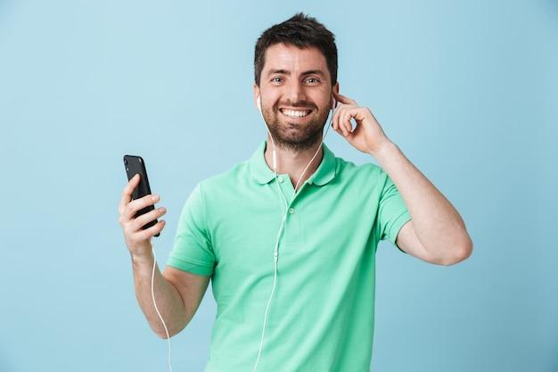 Bild eines glücklichen jungen gutaussehenden bärtigen mannes, der isoliert über blauer wand posiert und musik mit kopfhörern über das handy hört.