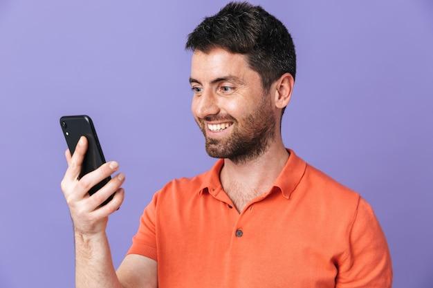 Bild eines glücklichen jungen gutaussehenden bärtigen mannes, der isoliert über violett-violetter wand mit handy posiert.