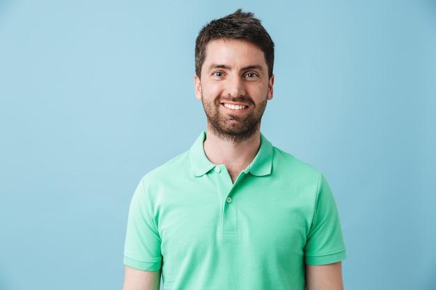 Bild eines glücklichen jungen gutaussehenden bärtigen mannes, der lokalisiert über blauer wand aufwirft.
