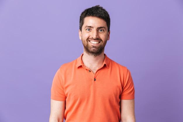 Bild eines glücklichen jungen gutaussehenden bärtigen mannes, der lokalisiert über violetter purpurroter wand aufwirft.