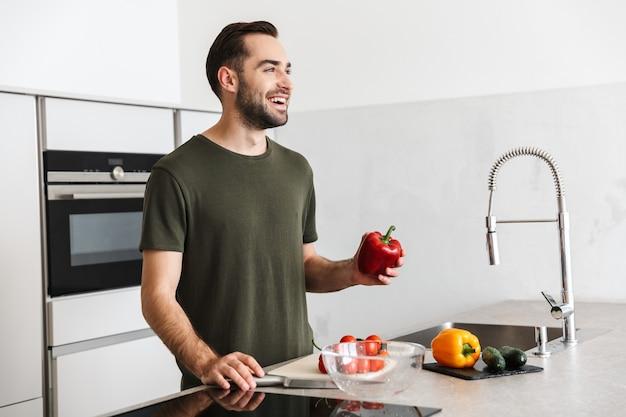Bild eines glücklichen jungen gutaussehenden mannes, der zu hause in der küche kocht, frühstücken.