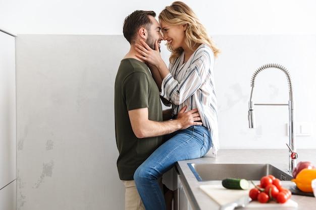 Bild eines glücklichen jungen liebespaares, das zu hause in der küche posiert und das küssen umarmt.