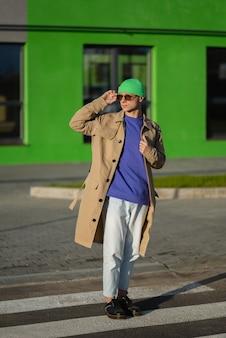 Bild eines glücklichen jungen mannes des hipsters in der freizeitkleidung hält sonnenbrille