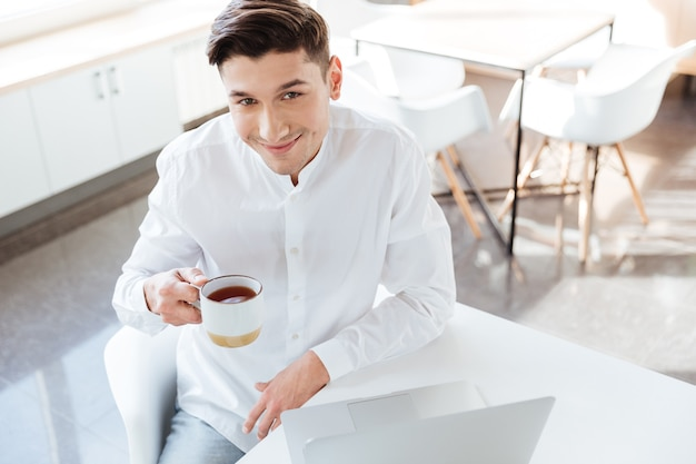Bild eines glücklichen mannes im weißen hemd mit laptop-computer beim kaffeetrinken gekleidet. coworking. blick in die kamera.