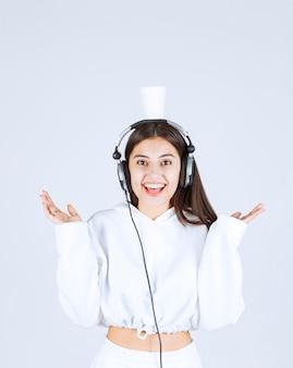 Bild eines glücklichen modells des jungen mädchens mit kopfhörern, die eine schale obenliegend halten
