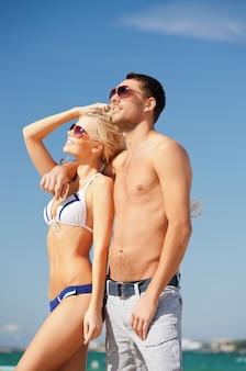Bild eines glücklichen paares mit sonnenbrille am strand (schwerpunkt mann)