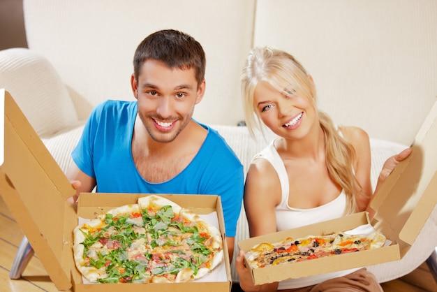 Bild eines glücklichen romantischen paares, das zu hause pizza isst (fokus auf den menschen) Premium Fotos