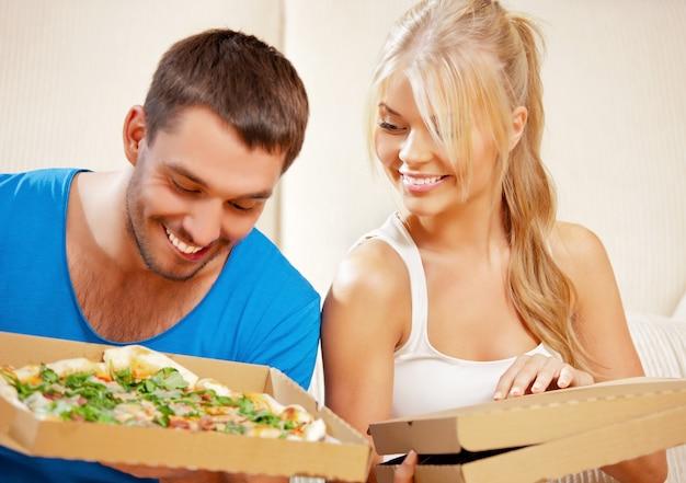 Bild eines glücklichen romantischen paares, das zu hause pizza isst (fokus auf frau)