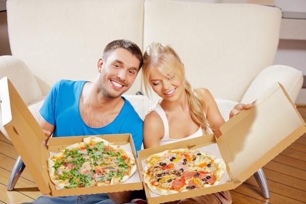 Bild eines glücklichen romantischen paares, das zu hause pizza isst