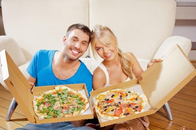 Bild eines glücklichen romantischen paares, das zu hause pizza isst Premium Fotos