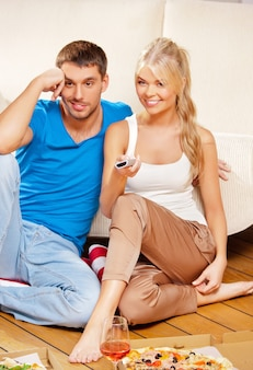 Bild eines glücklichen romantischen paares mit fernbedienung