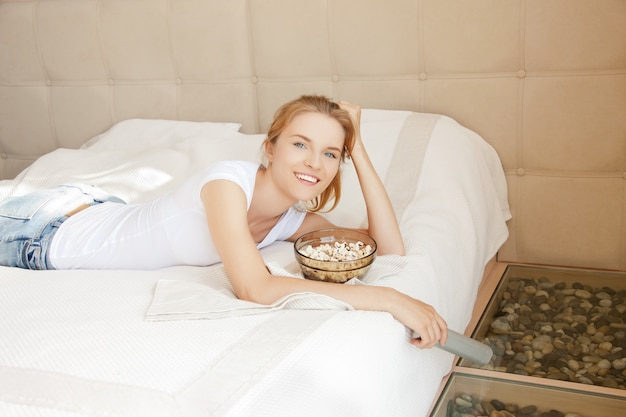 Bild eines glücklichen teenager-mädchens mit tv-fernbedienung und popcorn