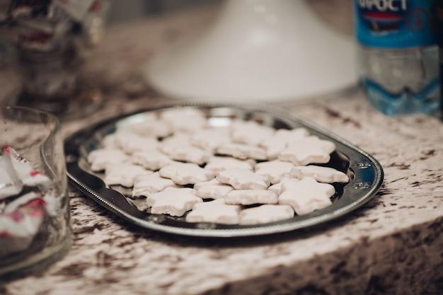 Bild eines großen silbernen tellers mit vielen hausgemachten weißen sternkeksen auf dem tisch
