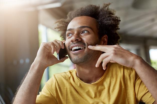 Bild eines gut aussehenden glücklichen afrikanischen mannes mit bart und lockigem haar, der fröhlich lächelt, während er auf handy spricht, interessierten blick hat