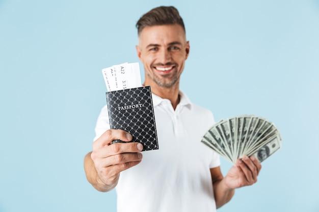 Bild eines gutaussehenden aufgeregten emotionalen erwachsenen mannes, der über blauer wand, die pass mit tickets und geld hält, aufwirft.