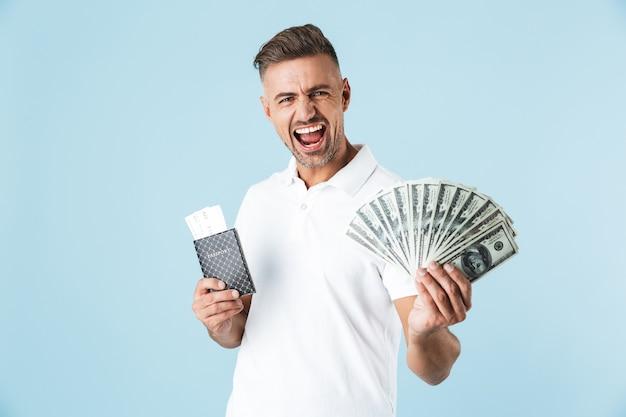 Bild eines gutaussehenden aufgeregten emotionalen schreienden erwachsenen mannes, der über blauer wand posiert, die pass mit tickets und geld hält.