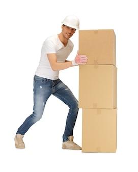 Bild eines gutaussehenden baumeisters, der große kisten bewegt.