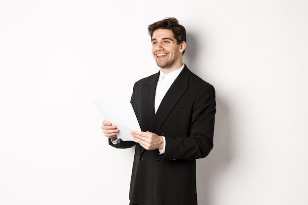 Bild eines gutaussehenden geschäftsmannes im anzug, der dokumente hält und lächelt und vor weißem hintergrund steht