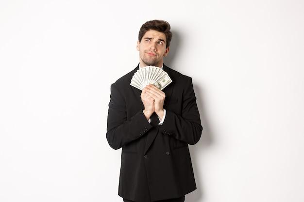 Bild eines gutaussehenden geschäftsmannes im schwarzen anzug, der geld hält und über investitionen nachdenkt, einkaufspläne macht, auf weißem hintergrund steht
