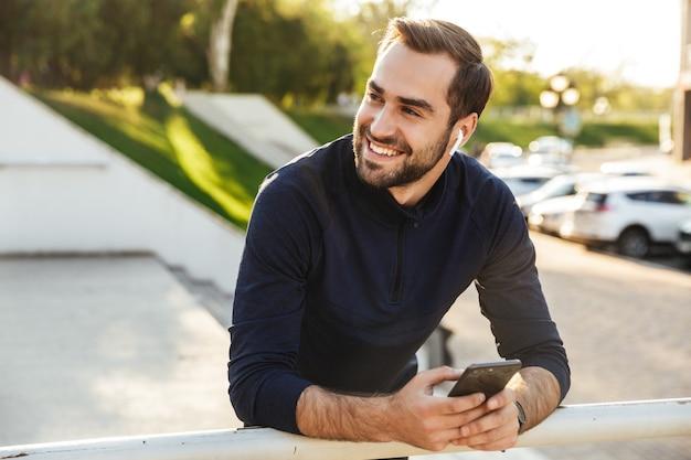 Bild eines gutaussehenden, glücklichen jungen, starken sportlers, der im freien am naturparkstandort posiert und musik mit kopfhörern auf dem handy hört.