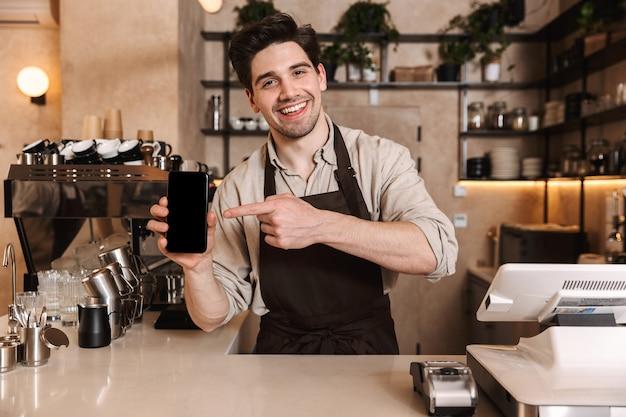 Bild eines gutaussehenden glücklichen kaffeemannes, der in der café-bar posiert, die drinnen arbeitet und die anzeige des mobiltelefons zeigt.