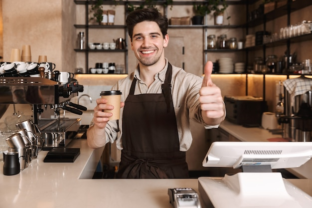 Bild eines gutaussehenden glücklichen kaffeemannes, der in der café-bar posiert, die drinnen arbeitet und eine kaffeetasse hält, die daumen nach oben zeigt.