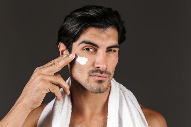 Bild eines gutaussehenden jungen mannes, der mit handtuch isoliert wird, kümmert sich um seine haut mit creme.